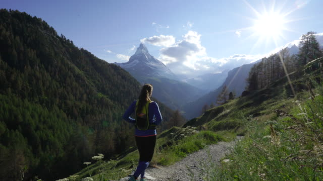 woman hikes alpine trail with sunset view of swiss matterhorn - strada in terra battuta video stock e b–roll