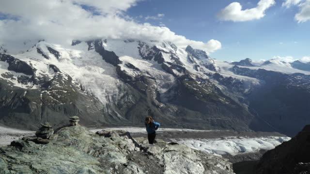 Kvinna vandringar berget ovanför glaciären