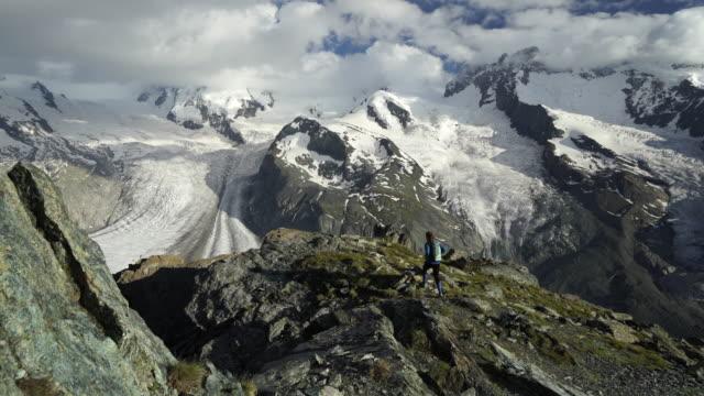 Kvinna vandringar till berget kant att ta magnifika utsikten