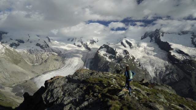 Kvinna vandringar till berget outlook och tar i magnifik utsikt över Gorner Glacier