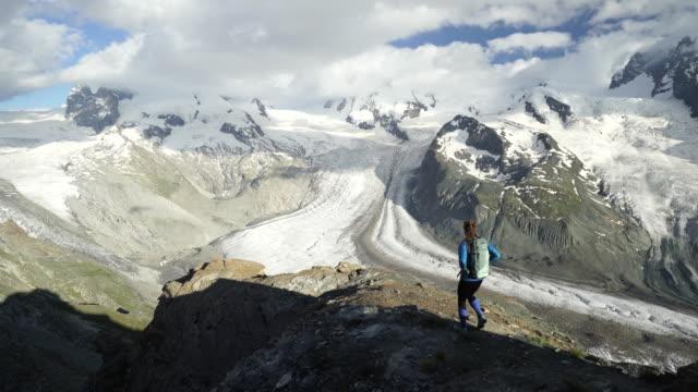 Kvinna vandringar till berget outlook och tar i magnifik utsikt