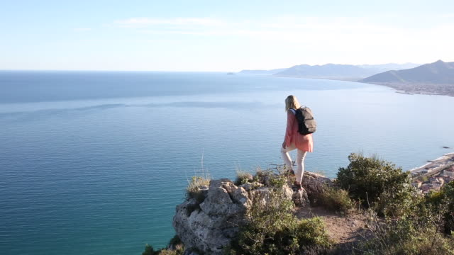 Woman hikes to rock ledge, looks out across sea and mountains