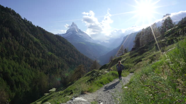 Woman hikes trail with sunny views of Swiss Matterhorn