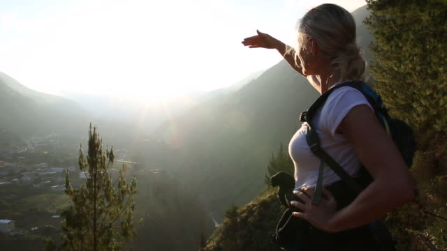 woman hikes up to valley overview, pauses to look off - sportschützer stock-videos und b-roll-filmmaterial