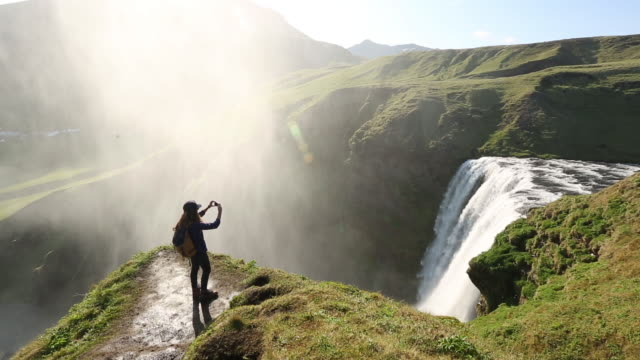 a woman hiking above skogafoss waterfall in iceland. - reykjavik stock videos and b-roll footage