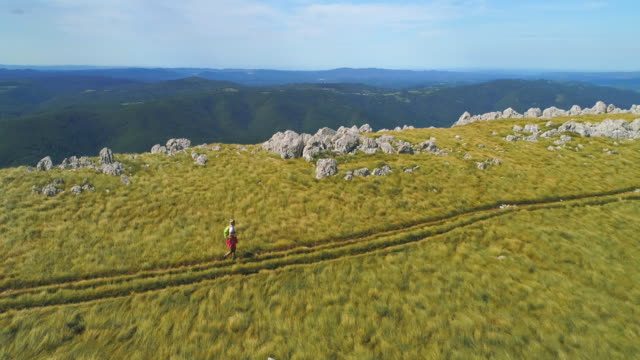 aerial woman hiking along a footpath on the nanos - slovenia stock videos & royalty-free footage