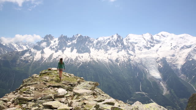 a woman hiking along a ridge in the french alps in early summer. - alpi video stock e b–roll