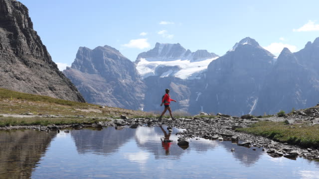 A woman hiking along an alpine lake with snowy mountains in the distance.