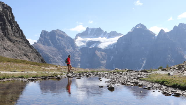 vídeos de stock, filmes e b-roll de a woman hiking along an alpine lake with snowy mountains in the distance. - top