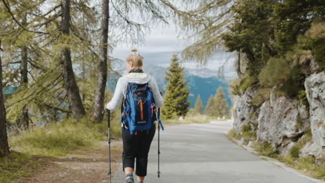 stockvideo's en b-roll-footage met slo mo vrouw die onderaan de bergweg wandelt - julian alps
