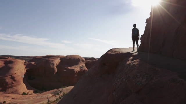 woman hiking in arches national park: delicate arch - utah stock videos & royalty-free footage
