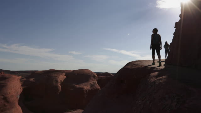 woman hiking in arches national park: delicate arch - arches national park stock videos & royalty-free footage