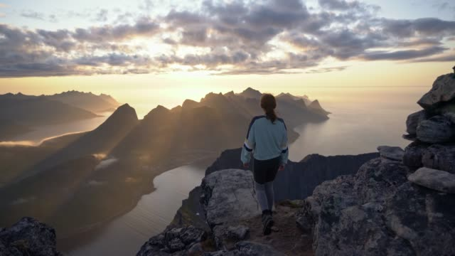 woman hiking  in mountains  on senja island in fog - traditionally norwegian stock videos & royalty-free footage