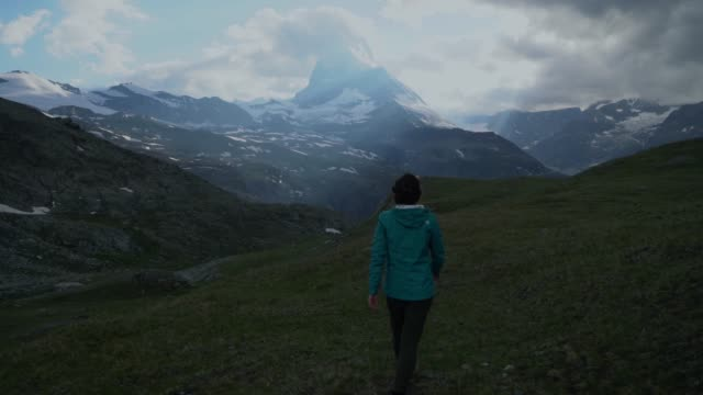 woman hiking in swiss alps near matterhorn - brown hair stock videos & royalty-free footage
