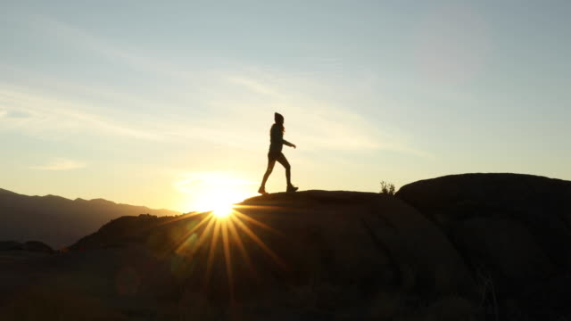 a woman hiking in the desert at sunrise. - utforskning bildbanksvideor och videomaterial från bakom kulisserna