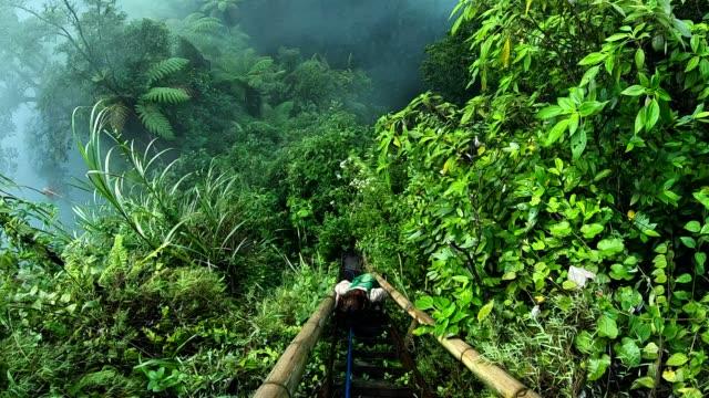 vidéos et rushes de femme randonnée dans les jungles sur java. images de la caméra portable - enjoyment