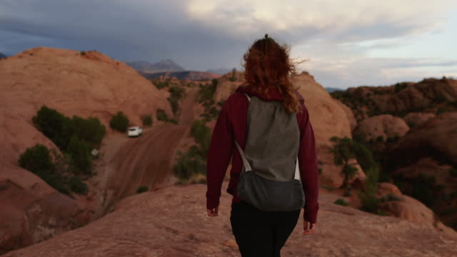 woman hiking in the majestic desert landscapes of south west usa: outdoors adventures - moab utah stock videos & royalty-free footage