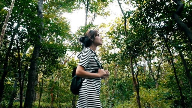 stockvideo's en b-roll-footage met vrouw wandelen in het bos - menselijke rug