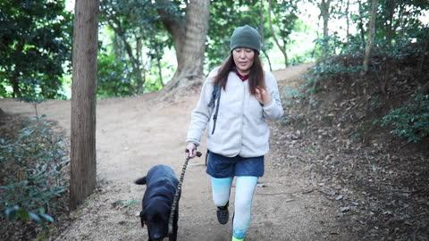 vidéos et rushes de randonnée de forêt de montagne de femme avec le crabot au ralenti - vie simple