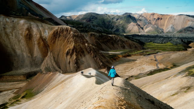Woman hiking near colorful mountains in Landmannalaugar in Iceland