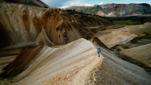 woman hiking near colorful mountains in landmannalaugar in iceland - geology stock videos & royalty-free footage