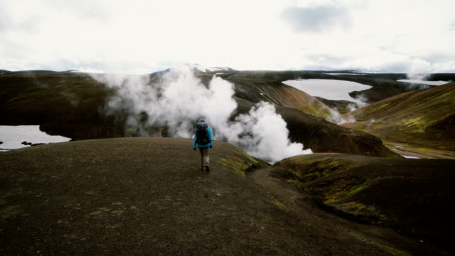 woman hiking near colorful mountains in landmannalaugar in iceland - geyser video stock e b–roll