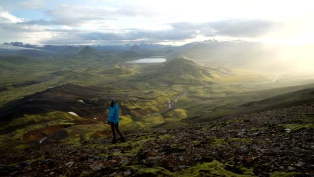 Frau in der Nähe von bunten Bergen in Landmannalaugar in Island Wandern