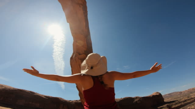 woman hiking near corona arch, in the great southwest usa - moab utah stock videos & royalty-free footage