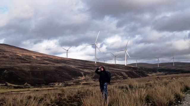 woman hiking near renewable energy wind turbines - carbon footprint stock videos and b-roll footage