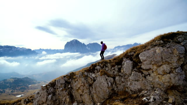Woman hiking near Seceda mountain in Dolomites