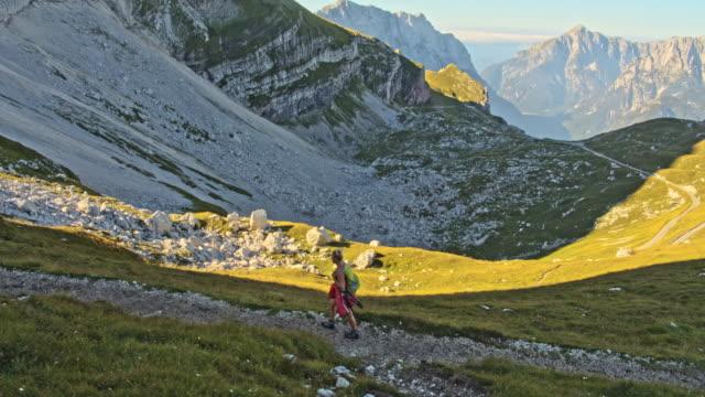 stockvideo's en b-roll-footage met ws vrouw wandelen op een bergpad in de julische alpen - julian alps