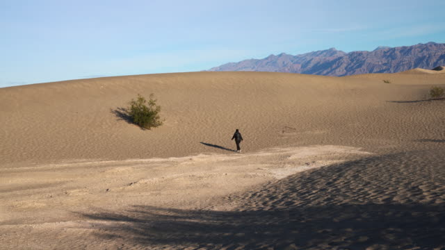woman hiking on sand dunes at mesquite flats, death valley, california. - death valley national park stock videos & royalty-free footage