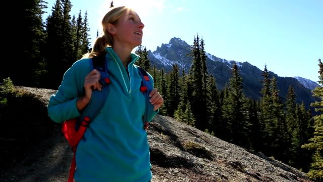 Frau Wandern auf trail Haltestellen an und bewundern Sie die Landschaft