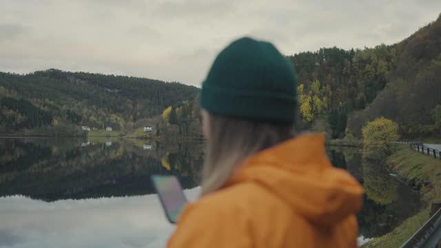 vídeos de stock, filmes e b-roll de mulher caminhando ao ar livre perto de um lago na noruega: folhagem de folhas de outono - países nórdicos