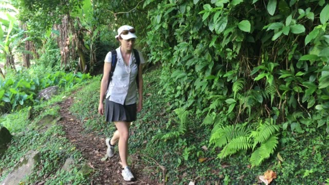 Woman hiking the Cross Island Track in the rain forest of a tropical pacific island