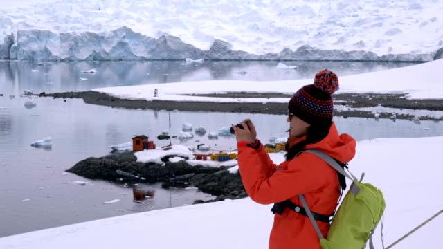 vidéos et rushes de femme de randonnée à travers la neige et la glace dans l'antarctique. - manteau et blouson d'hiver