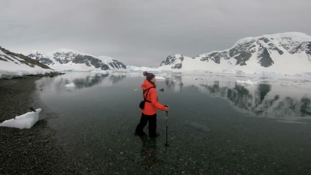 Woman hiking through ice and snow in Antarctica.