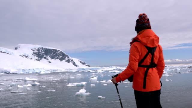 vidéos et rushes de femme de randonnée à travers la neige et la glace dans l'antarctique. - manteau et veste