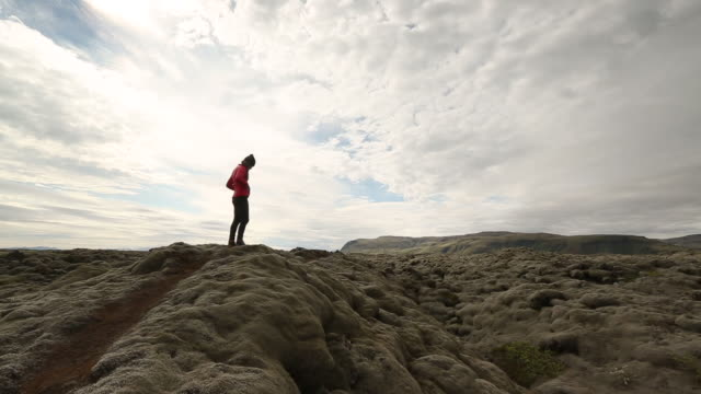 Woman hiking through moss-covered lava field in Iceland