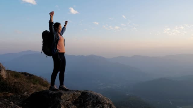 woman hiking to the mountain peak and hands up on head celebrating successful , slow motion - leisure activity stock videos & royalty-free footage