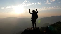 Woman hiking to the Mountain peak and hands up on head celebrating successful , SLOW MOTION