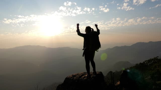 woman hiking to the mountain peak and hands up on head celebrating successful , slow motion - silhouette stock videos & royalty-free footage