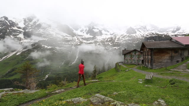 A woman hiking towards a mountain chalet in the Swiss Alps.
