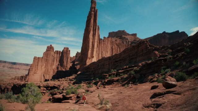 woman hiking under the fisher towers, southwest usa - canyon stock videos & royalty-free footage