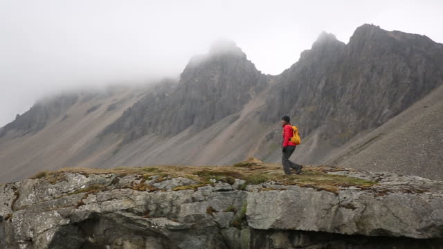 Woman hiking with a backpack along a rocky cliff in Iceland with mountains in the background