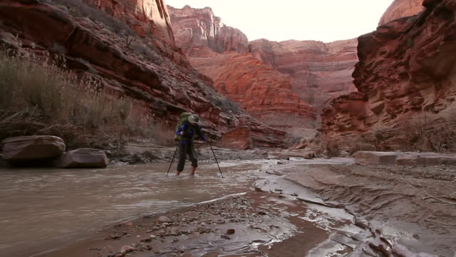 Woman hiking with backpack through river in deep red rock desert slot canyon.