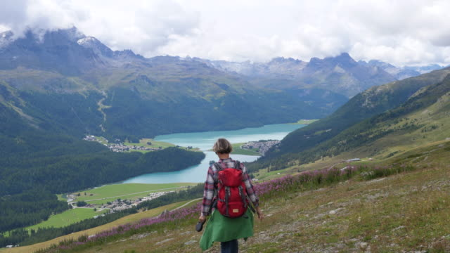 woman hiking with the dog in engadin, switzerland - dramatic landscape stock videos & royalty-free footage