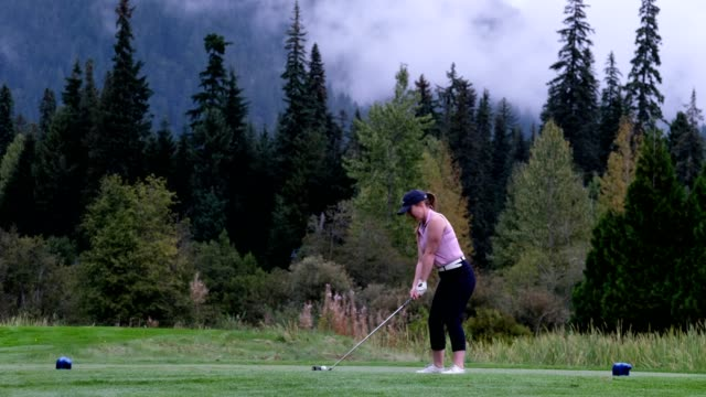 woman hits the perfect golf shot - golf swing women stock videos & royalty-free footage