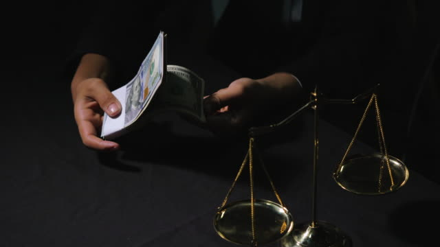 woman hold stack of usa currency with scale of justice - defendant stock videos & royalty-free footage