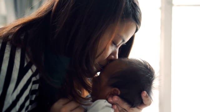 woman holding a baby and kisses him - carrying stock videos & royalty-free footage